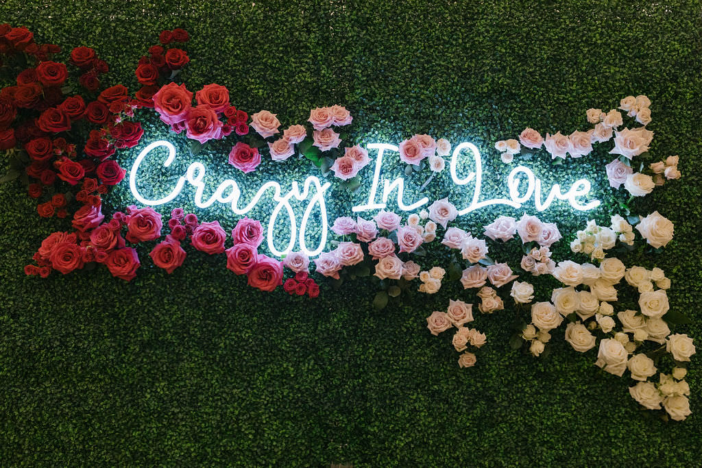 Crazy In Love Neon Sign on Greenery Wall Backdrop Outlined with Red, Blush Pink and Ivory Roses   Tampa Bay Wedding Florist Bruce Wayne Florals   St. Pete Wedding Planner Parties A'la Carte