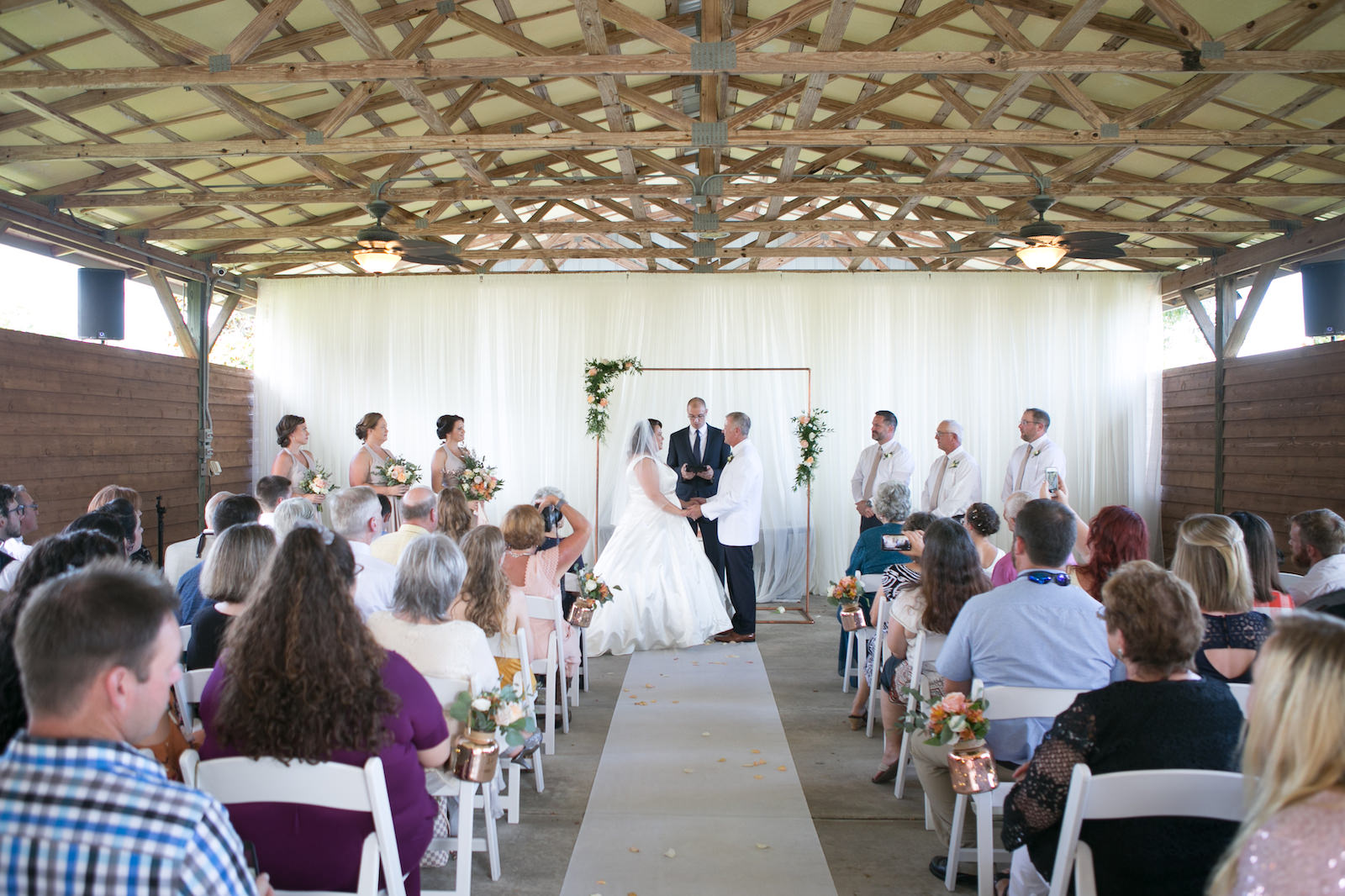Tampa Bride and Groom Exchanging Wedding Vows During Ceremony Under Copper Arch | Wedding Photographer Carrie Wildes Photography | Pinellas Park shahnasarian hall | Wedding Dress Truly Forever Bridal