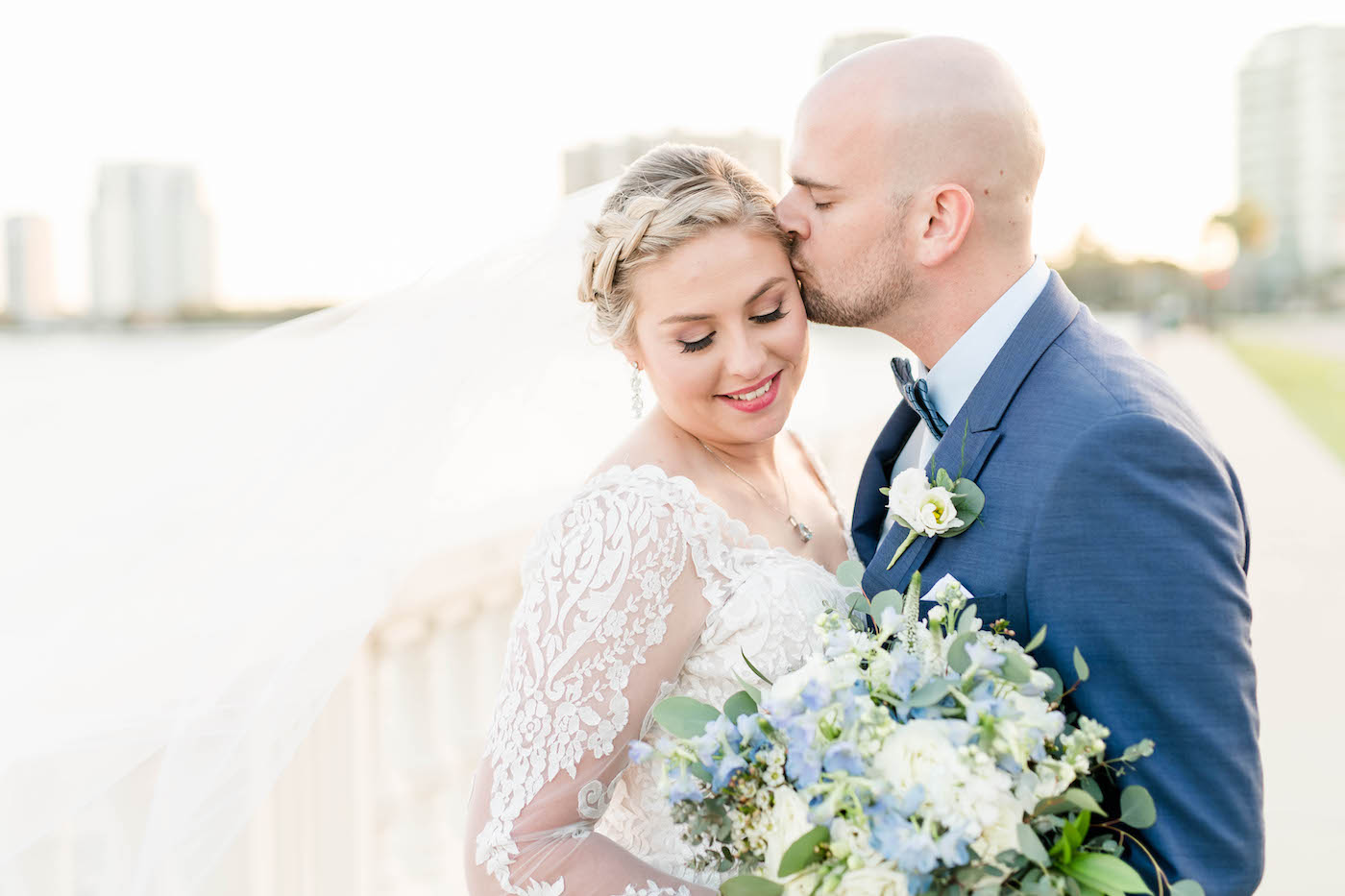 Bride and Groom Outdoor Portraits with Veil Shot   Ivory Lace Long Sleeve V Neck Bridal Gown and Groom in Blue Suit with Bow Tie   Blue and White Bridal Bouquet   Femme Akoi Beauty Studio
