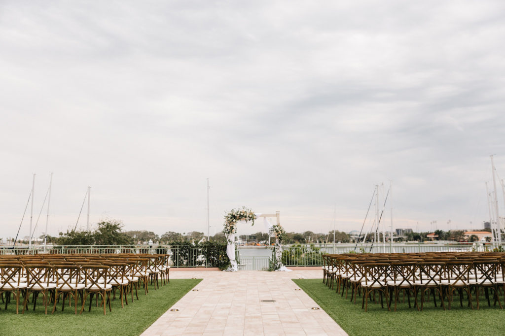 Boho Chic Outdoor Waterfront Ceremony, Wooden Cross back Chairs, Altar with White Linen Draping, Decorated with Lush Ivory Flowers and Blush Pink Roses, Pampas Grass Bouquets with Greenery | The Esplanade Location of the Vinoy Renaissance Resort in Downtown St. Petersburg | Tampa Bay Luxury Wedding Planner Parties A' La Carte | Rentals A Chair Affair and Over the Top Linens
