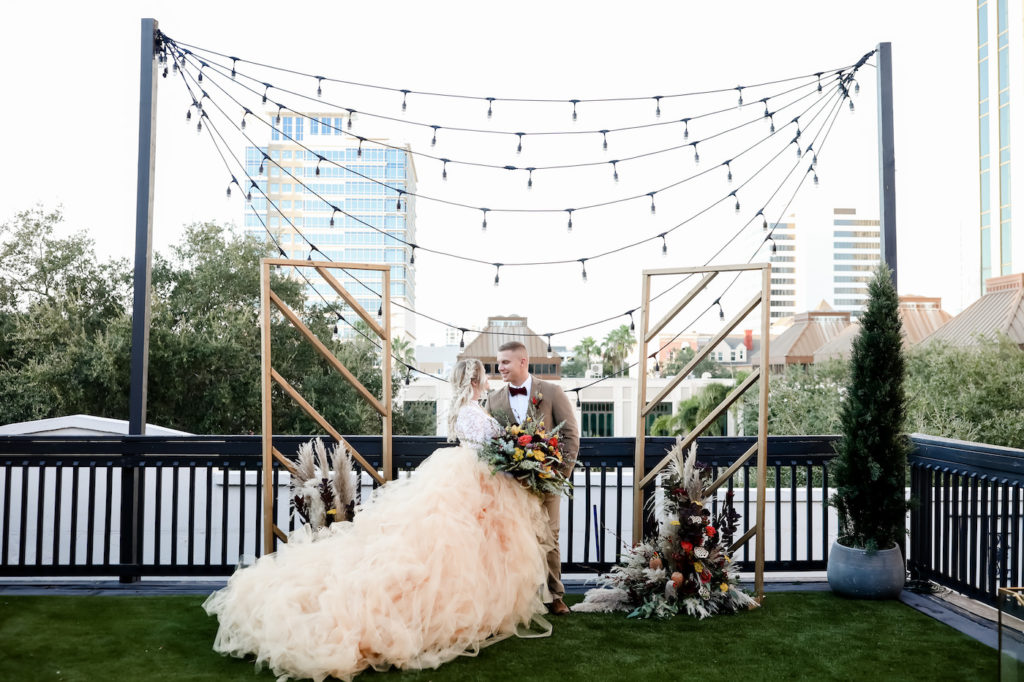 Bohemian Inspired Tampa Bay Bride and Groom Wedding Portrait, In front of Ceremony Backdrop with String Lighting and Outdoor City View, Vintage Wedding Decor with Wooden Alters, Boho Bride Wearing Oversized Blush Orange Long Tulle Skirts, White Lace Long Sleeve Top, Holding Vintage Wildflower Bouquet, with Orange, Purple, Yellow, Red, Eggplant and Ivory Floral Stems, Thistle, Roses, Groom in Brown Suit with Velvet Bowtie | Tampa Bay Wedding Planner Blue Skies Weddings and Events | Downtown St. Petersburg Wedding Photographer Lifelong Photography Studio | Unique Florida Wedding Venue Station House in DTSP