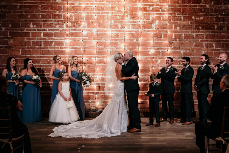 Florida Bride and Groom Intimate Exchange and Kiss During Wedding Ceremony, Interior Summer Ceremony with Exposed Red Brick Wall and String Lighting | Historic Tampa Bay Industrial Wedding Venue NOVA 535 in Downtown St. Petersburg