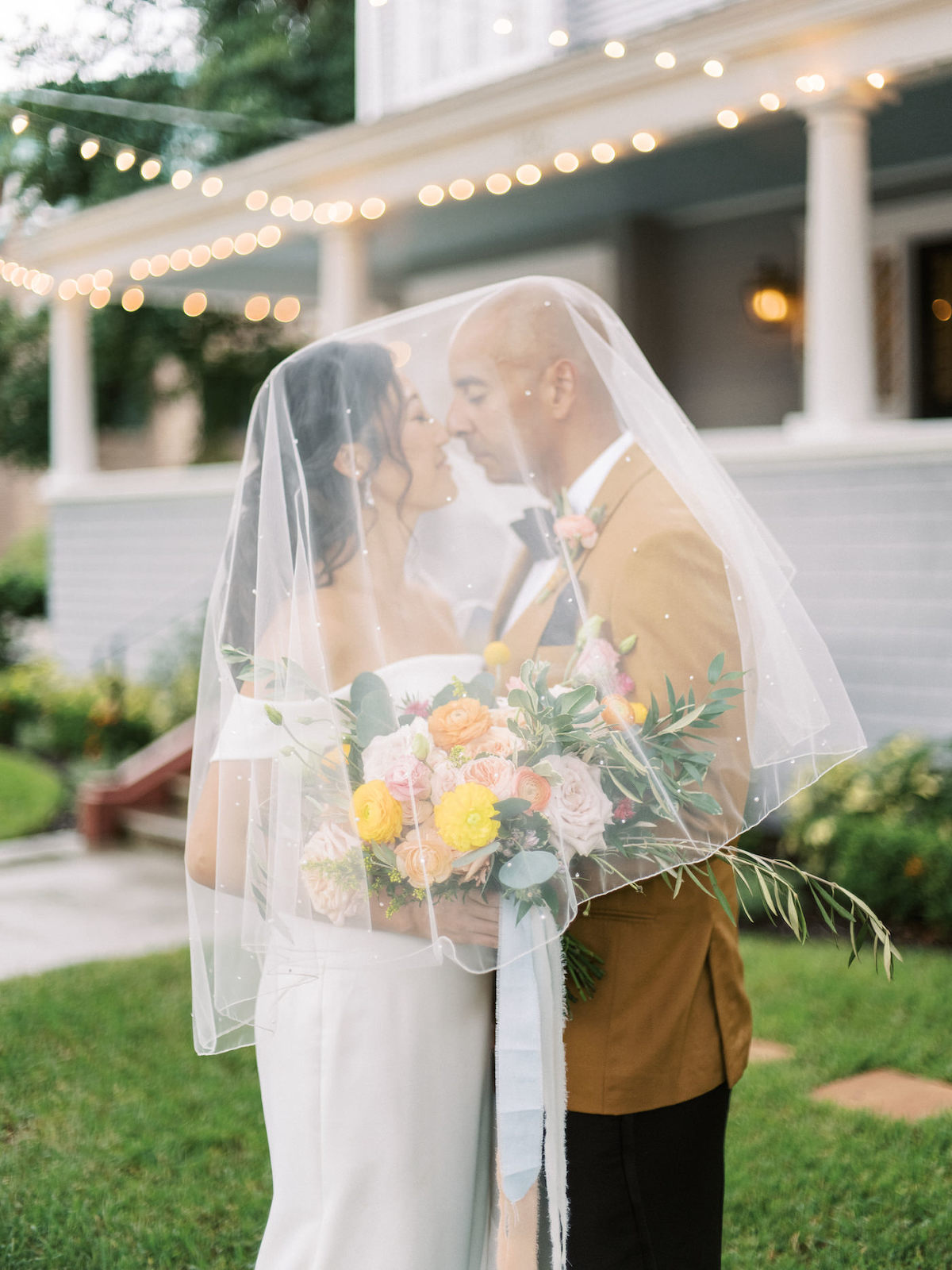 Tampa Bay Bride and Groom Intimate Portrait Under Bridal Veil During Cocktail Hour, Holding Vibrant Bouquet with Yellow, Pink, and Peach Floral Stems with Greenery | Florida Wedding Planner Kelly Kennedy Weddings and Events