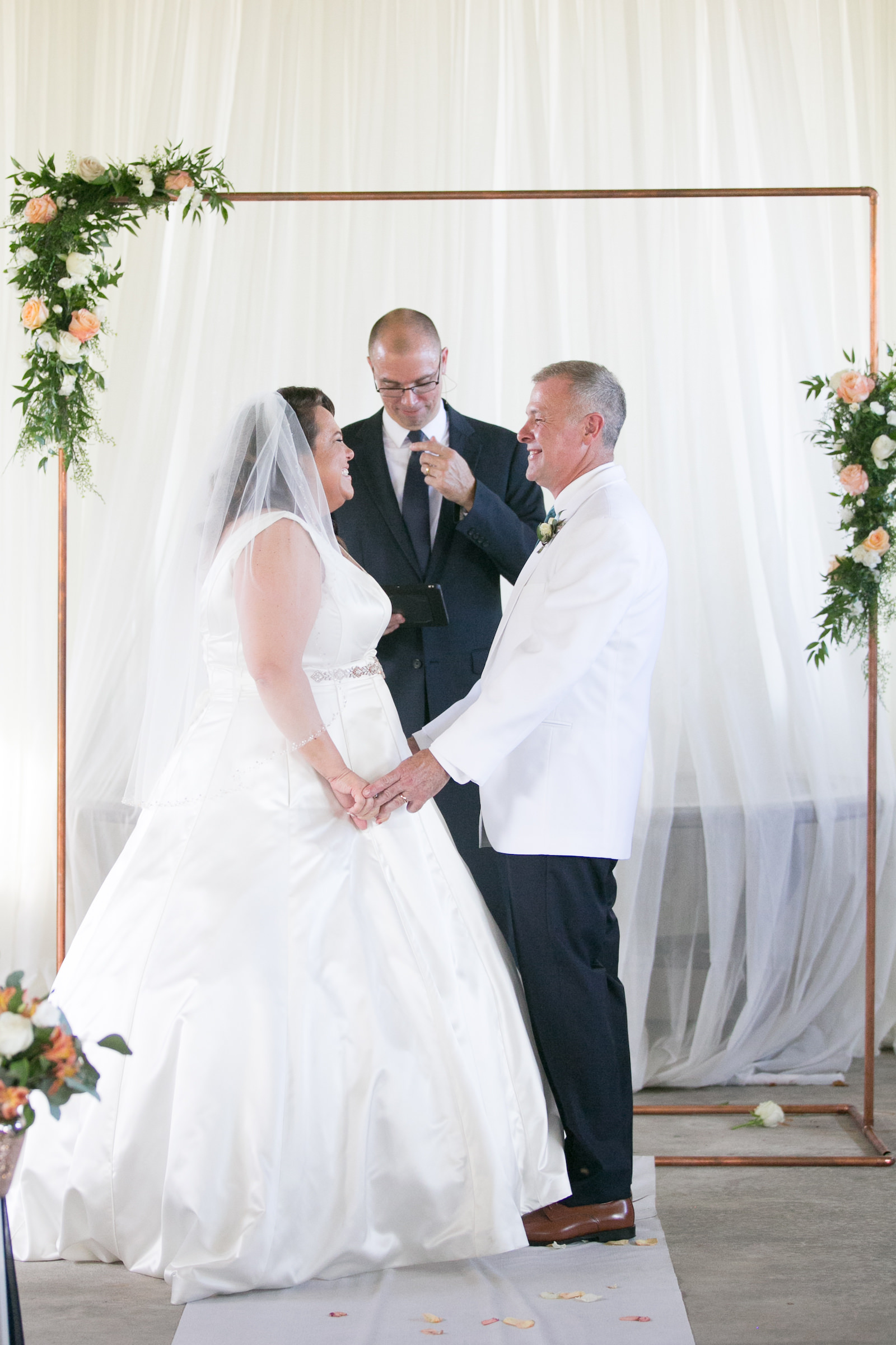 Tampa Bride and Groom Under Copper Arch Exchanging Wedding Vows During Ceremony Portrait | Wedding Photographer Carrie Wildes Photography | Wedding Dress Truly Forever Bridal