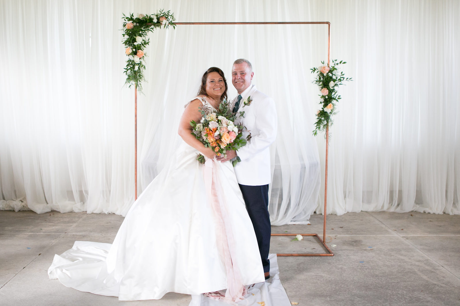 Tampa Bride Holding Spring Color Floral Bouquet with Blush Pink Ribbon and Groom Wedding Portrait Under Copper Arch | Wedding Photographer Carrie Wildes Photography | Wedding Hair and Makeup Michele Renee the Studio | Wedding Dress Truly Forever Bridal