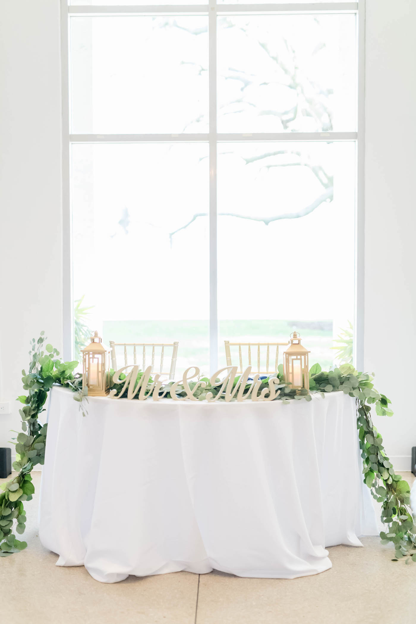 Wedding Sweetheart Table with Greenery Garland and Lanterns and Mr and Mrs Tabletop Signs   Gabro Event Services