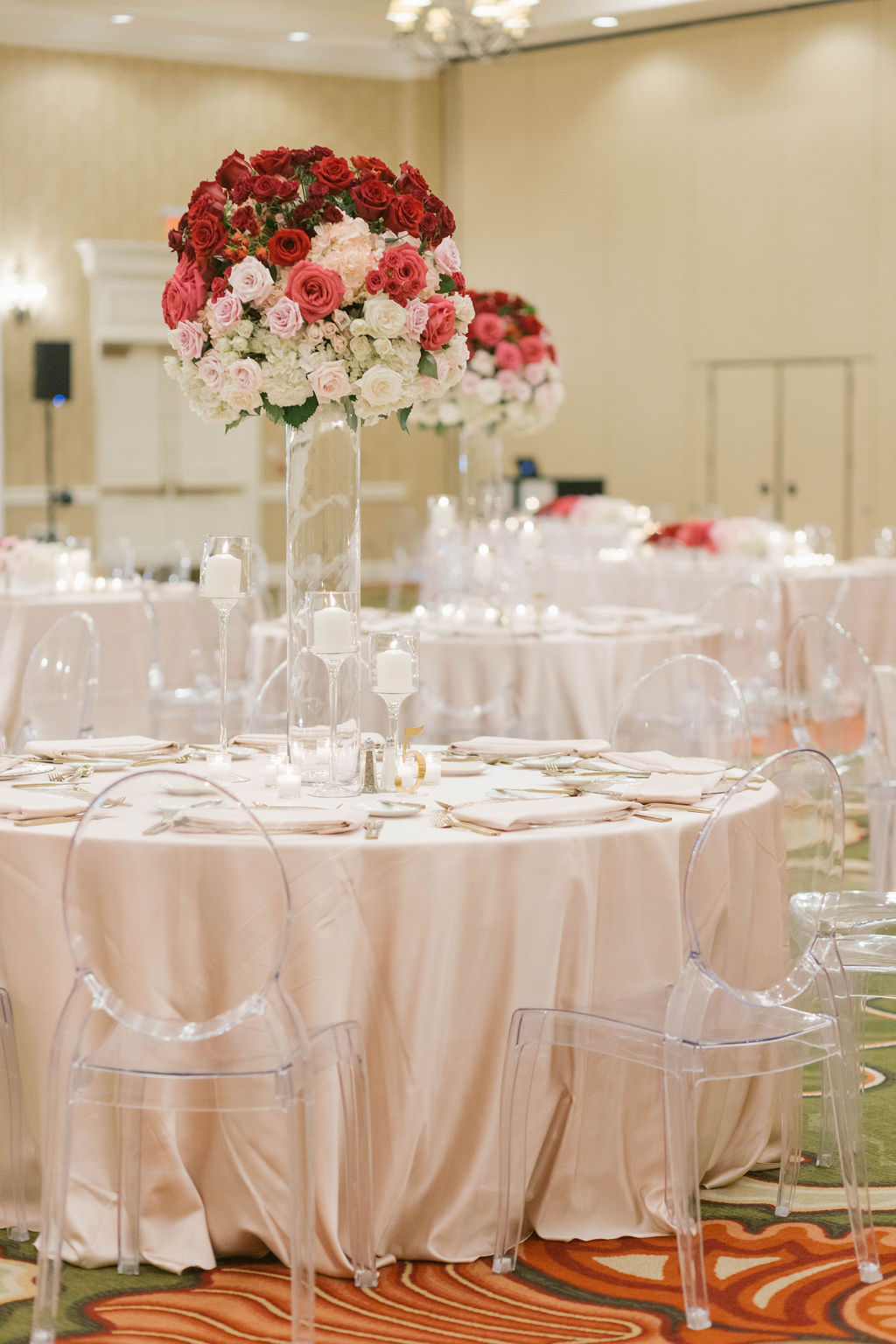 Romantic Ballroom Wedding Reception Decor, Round Table with Ivory Linen, Ghost Acrylic Chairs, Tall Red, Blush Pink and White Roses Floral Centerpieces   St. Petersburg Wedding Venue The Vinoy Renaissance   Tampa Wedding Planner Parties A'la Carte   Wedding Florist Bruce Wayne Florals   Wedding Rentals A Chair Affair   Draping Gabro Event Services   Over the Top Rental Linens