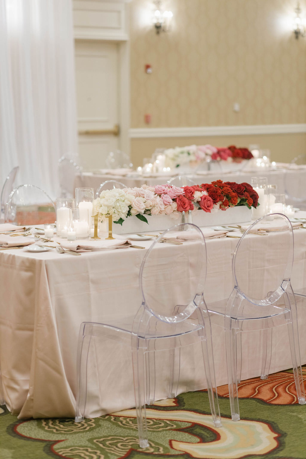 Romantic Wedding Reception Decor, Long Table with Light Pink Linens, Gold Flatware, Red, Blush Pink and Ivory Roses and Hydrangeas in White Planter Box Centerpiece and Ghost Acrylic Chairs   Tampa Bay Wedding Planner Parties A'la Carte   St. Pete Wedding Florist Bruce Wayne Florals   Wedding Rentals A Chair Affair   Over the Top Rental Linens