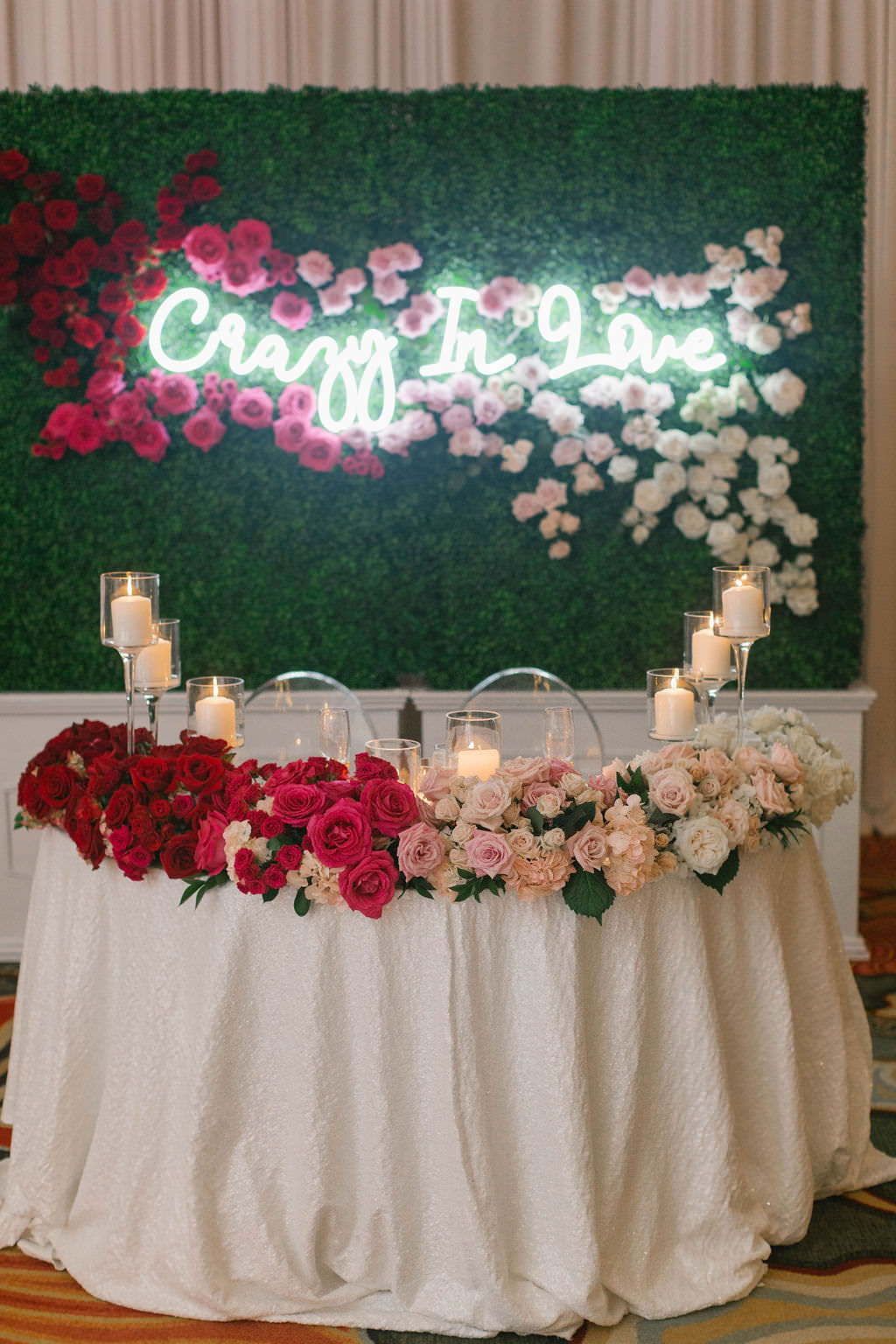 Romantic Wedding Reception Decor, Sweetheart Table with White Linen, Red, Blush Pink and Ivory Roses, Glass Candlesticks, Greenery Wall Backdrop with Crazy In Love Neon Sign and Roses   Tampa Bay Wedding Planner Parties A'la Carte   St. Pete Hotel Wedding Venue The Vinoy Renaissance   Wedding Florist Bruce Wayne Florals   Wedding Rentals A Chair Affair   Over the Top Rental Linens