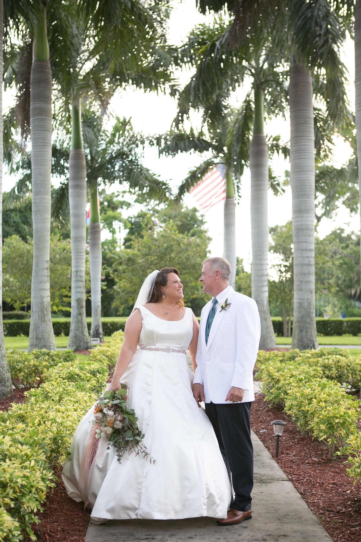 Tampa Bride in Ballgown Wedding Dress with Scooped Neckline and Belt, Groom in White Suit Wedding Portrait | Wedding Photographer Carrie Wildes Photography | Wedding Dress Truly Forever Bridal