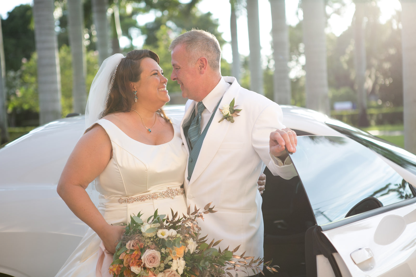 Tampa Bride in Scoop Neckline Wedding Dress with Rhinestone Belt Holding Spring Color Floral Bouquet, Groom in White Suit and Teal Vest | Wedding Photographer Carrie Wildes Photography | Wedding Dress Truly Forever Bridal | Wedding Hair and Makeup Michele Renee the Studio