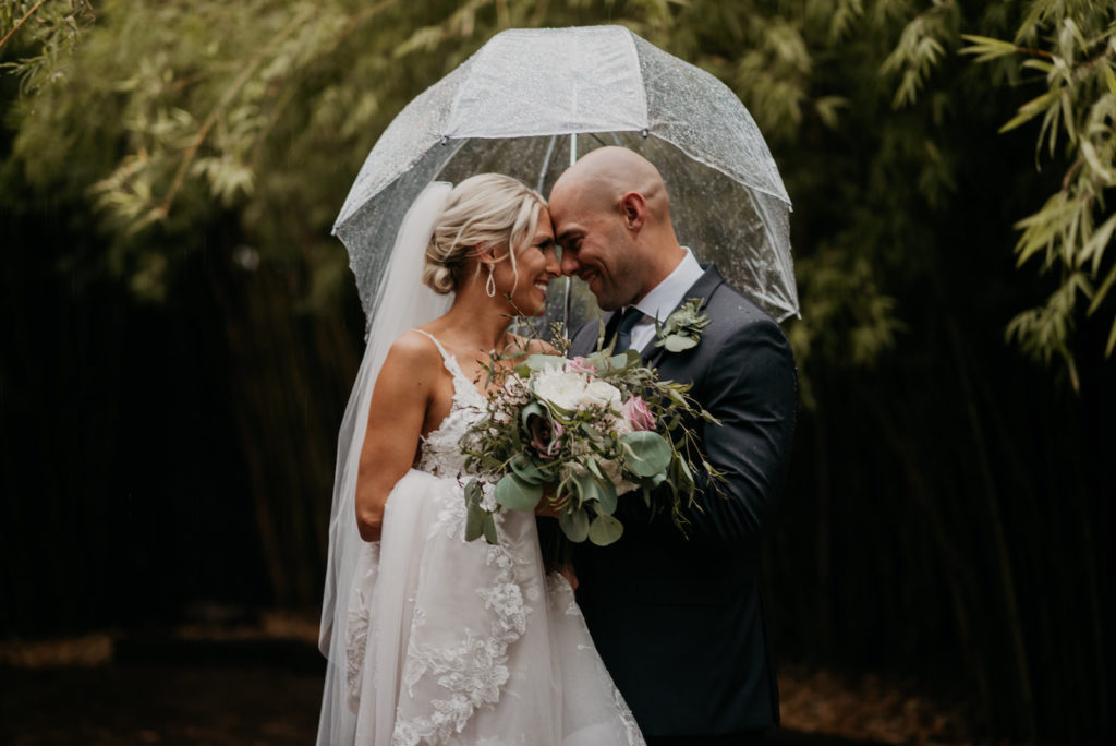 Downtown St. Pete Bride and Groom Wedding Portrait in The Rain, Holding Romantic Bridal Bouquet with White and Pink Roses, and Greenery Eucalyptus, Under Clear Umbrella | Historic Florida Wedding Venue NOVA 535