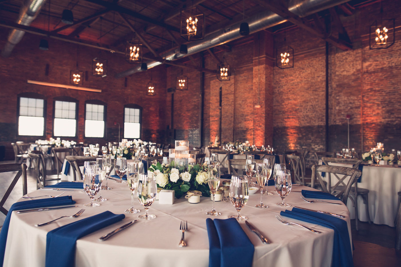 Tampa Wedding Reception Tables With Cobalt Blue Napkins And Greenery Floating Candle Centerpieces In Historic Venue Armature Works Unique Architecture With Brick Walls And Exposed Beam Ceilings With Edison Bulb Chandeliers
