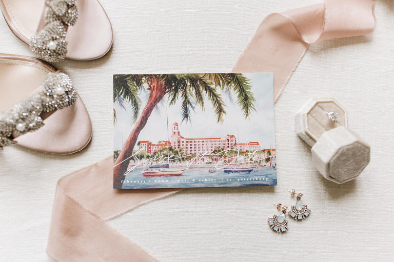 Luxury Florida Save the Date, Watercolor Portrait of Waterfront Vinoy Renaissance Resort in Downtown St. Petersburg, Bridal Wedding Accessores, Diamond Solitaire Engagement Ring in Cream Velvet Ring Box, Teal Boho Chic Earrings, Crystal Floral Strappy Sandal Wedding Shoes | Tampa Bay Wedding Planner Parties A' La Carte