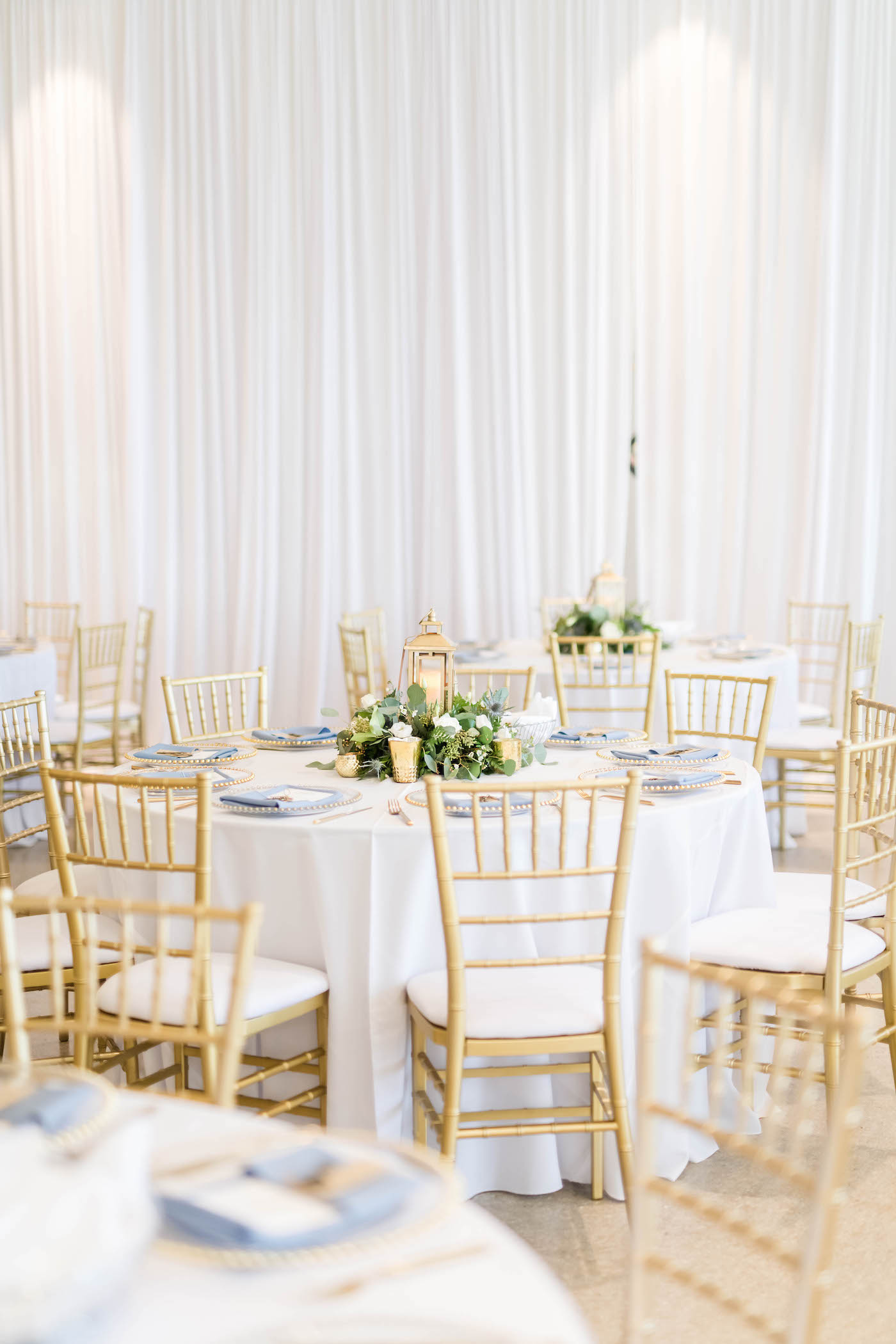 Tampa Wedding Venue the Tampa Garden Club Indoor Reception   Wedding Reception Tables with White Linens and Gold Chiavari Chairs and Low Greenery and Lantern Centerpieces   Gabro Event Services   Lynn's Catering of Tampa