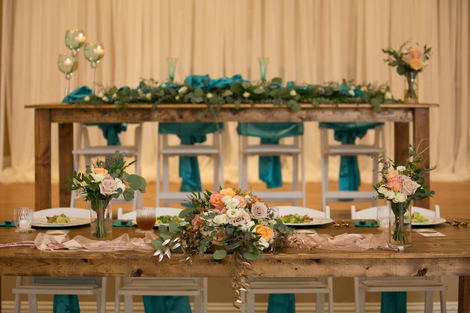 Rustic Wedding Reception Decor, Long Wooden Tables with Blue Teal Chair Sashes, Pink Orange and Mauve Roses, White Florals and Greenery Bouquets, Eucalyptus Table Runner | Wedding Photographer Carrie Wildes Photography | Wedding Linens Gabro Event Services
