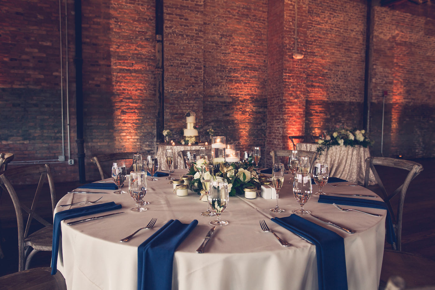 Tampa Wedding Reception Tables With Cobalt Blue Napkins And Greenery And White Floral Floating Candle Centerpieces Brick Walls With Amber Uplighting Marry Me Tampa Bay Local Real Wedding Inspiration