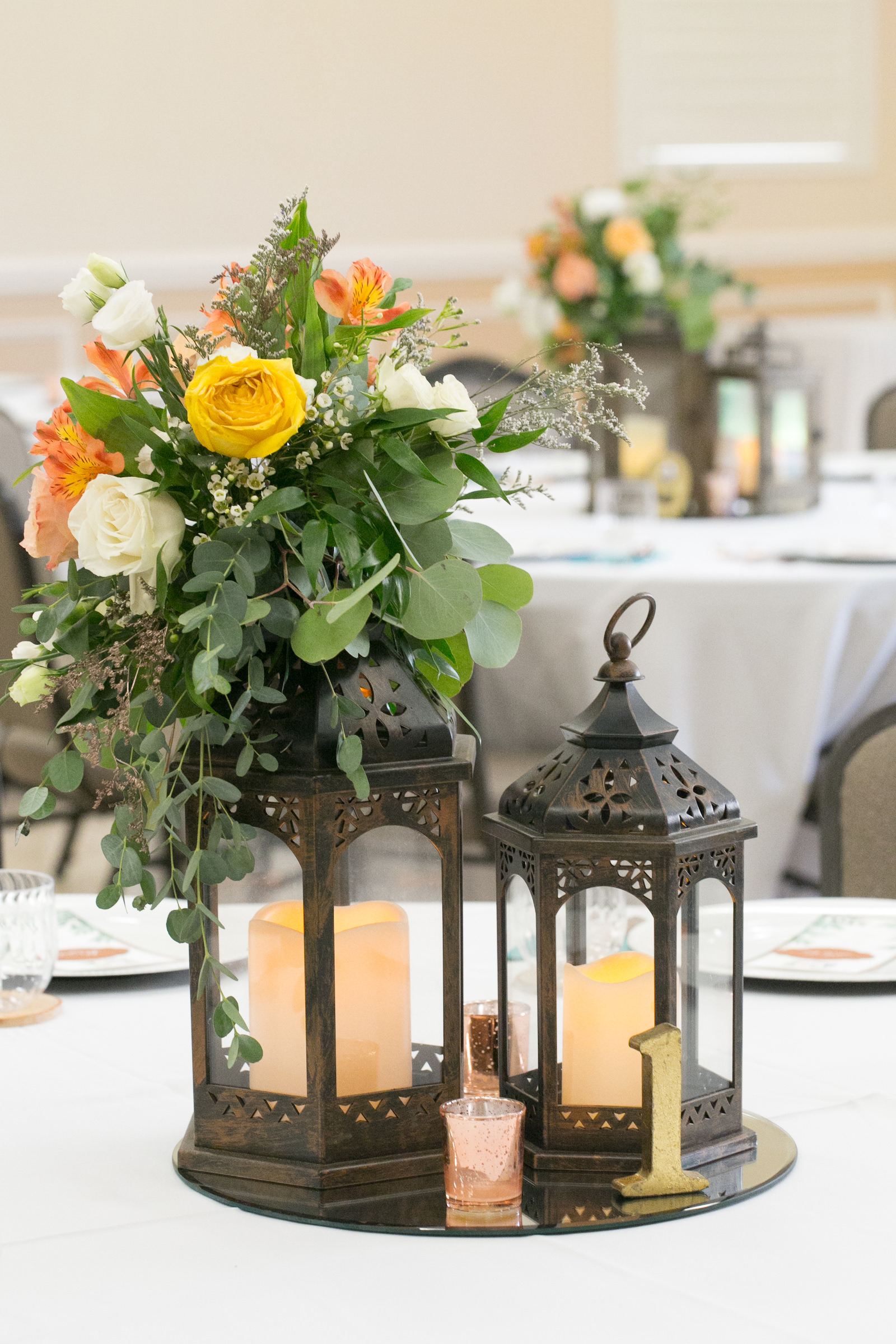 Rustic Wedding Reception Decor, Circular Mirror Tray with Black Lanterns and Candles, Yellow, Orange, and White Roses with Greenery Florals Centerpiece | Wedding Photographer Carrie Wildes Photography