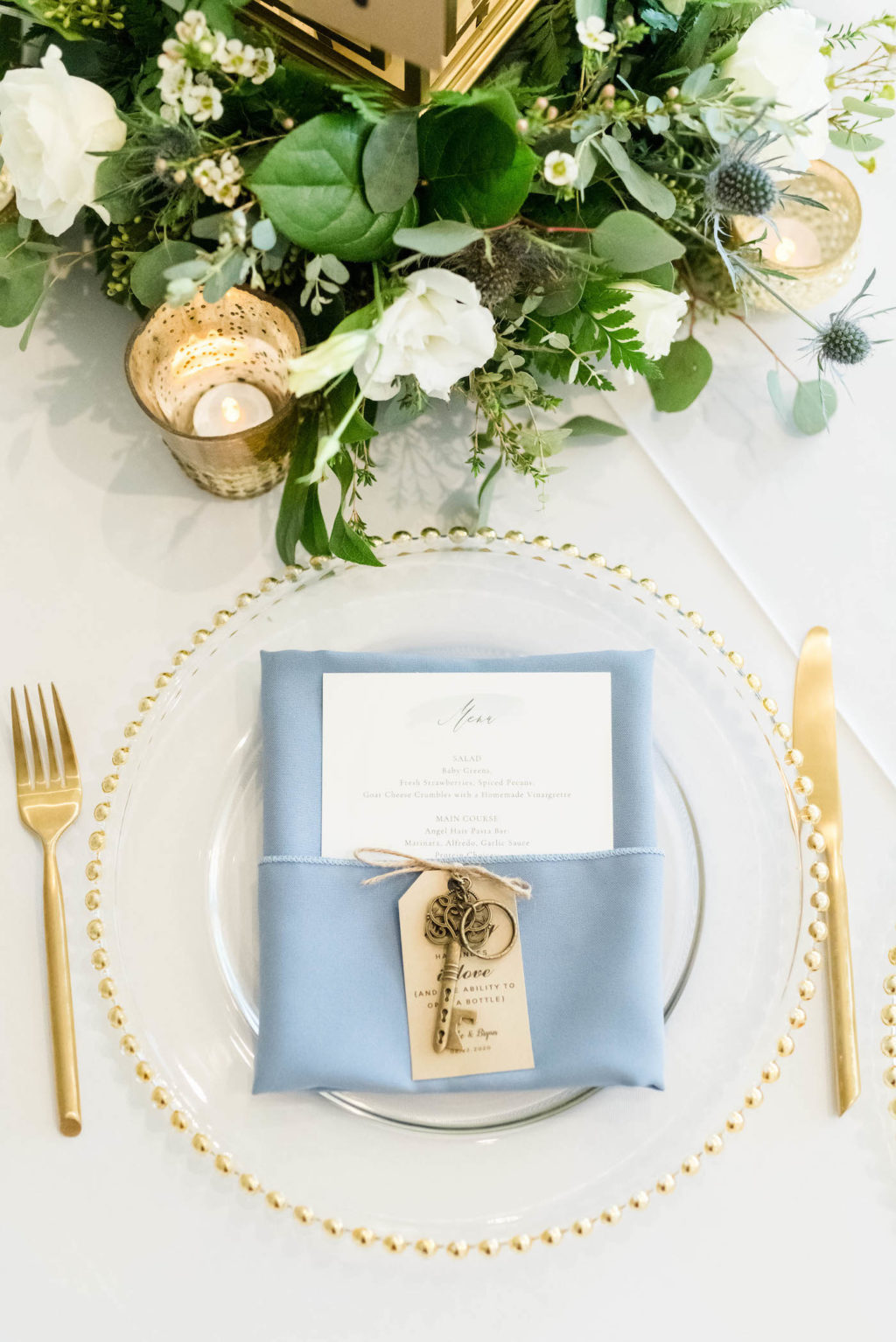 Wedding Place Setting with Gold Flatware and Gold Beaded Edge Glass Charger Plate and Dusty Blue Napkin with Menu and Brass Key Favor | Gabro Event Services | Lynn's Catering of Tampa