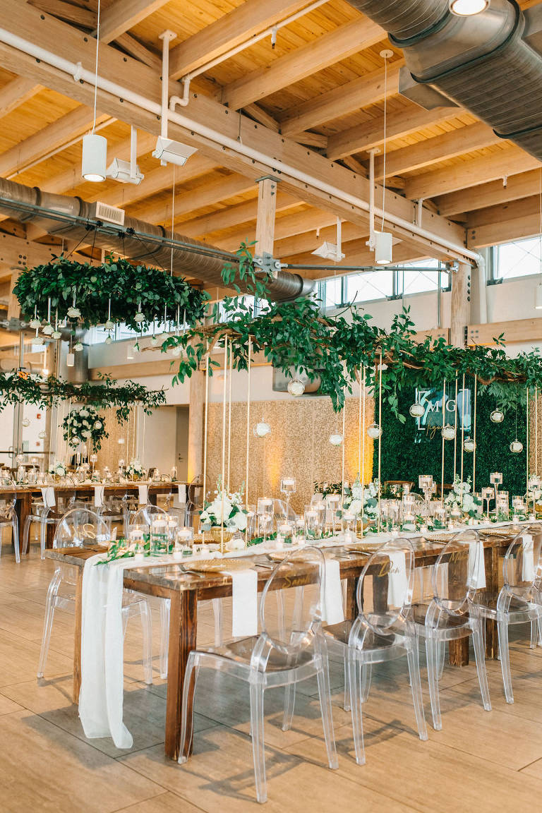 Modern, Garden Inspired Florida Wedding Reception and Decor at Tampa River Center, Long Wooden Feasting Tables with Clear Acrylic Ghost Chairs, White Linen Table Runners, Suspended Hanging Floral Arrangement, Greenery Garland with Ivory Flowers   Downtown Tampa Wedding Planner UNIQUE Weddings and Events   Florida Special Event Rental Company Over The Top Linens   Tampa Bay Decor Rental A Chair Affair   Over the Top Rental Linens