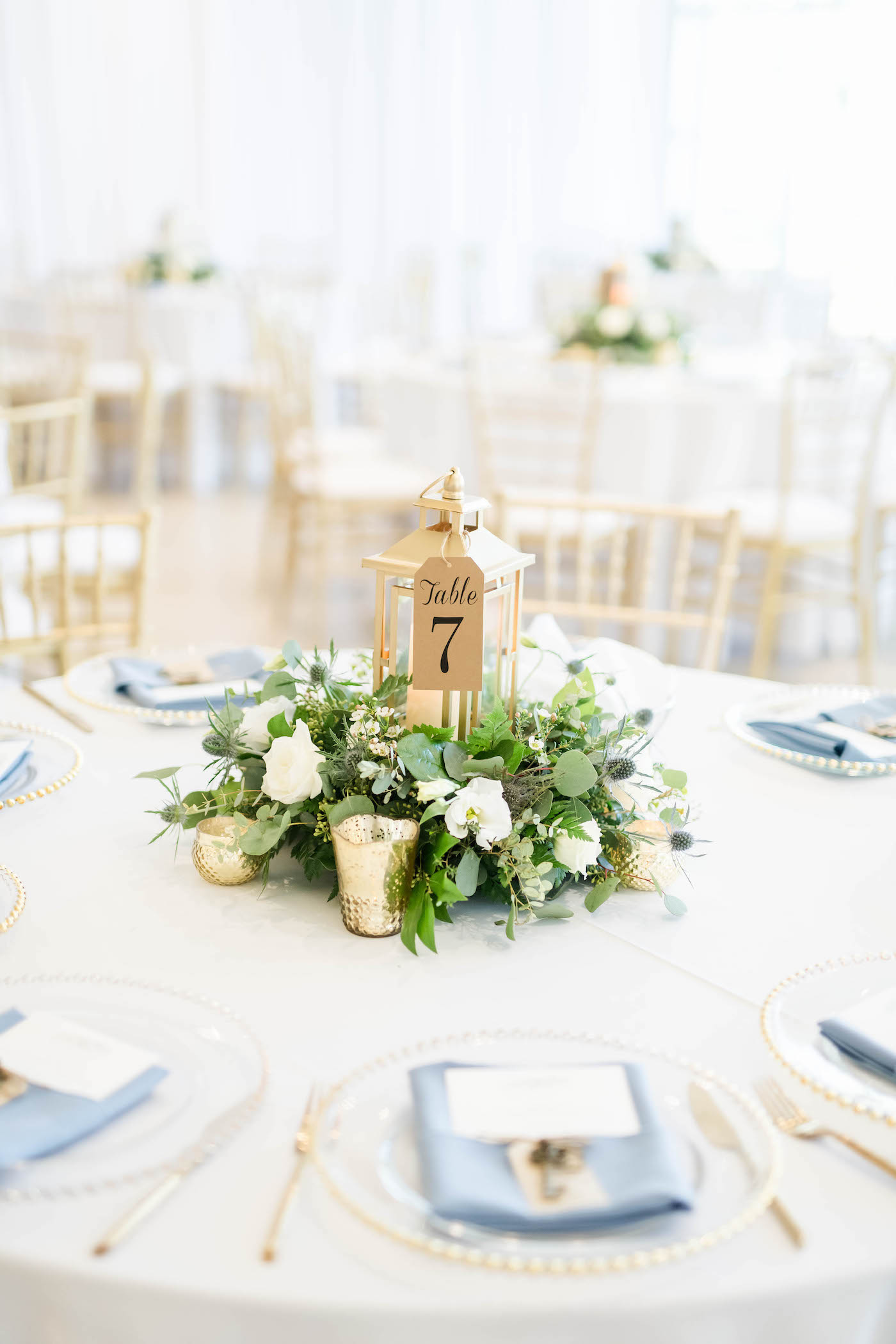Wedding Centerpiece with Lantern and Greenery with Gold Votive Candles and Kraft Paper Table Number Tag   Dusty Blue and White and Gold Wedding