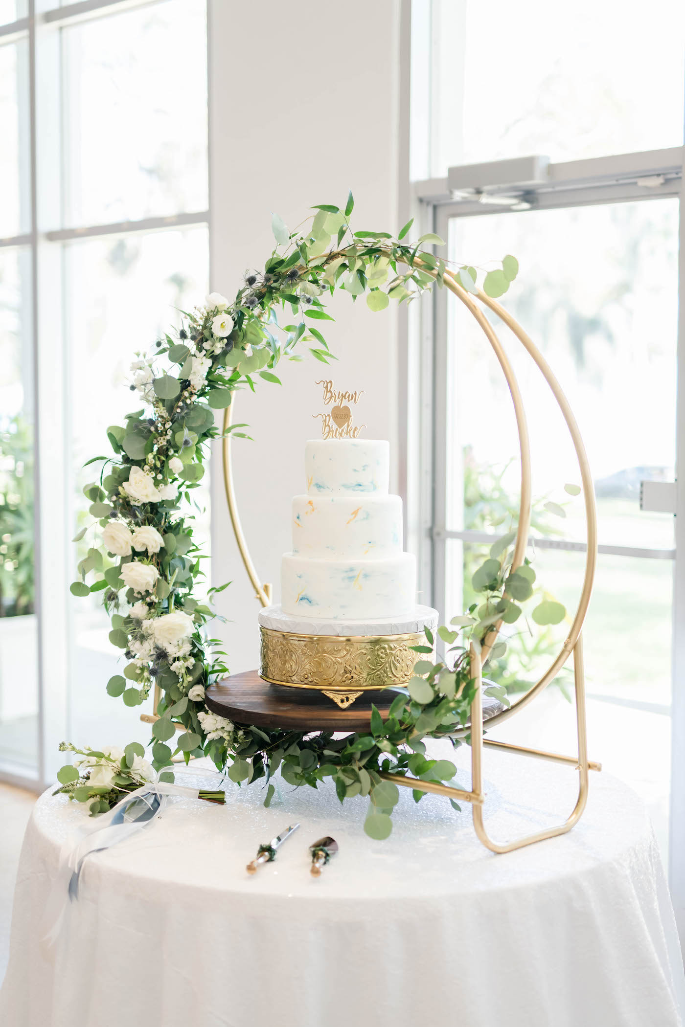 Wedding Cake Table Display with Unique Gold Moon Stand accented with Greenery Garland   Three Tier Fondant Wedding Cake with Marbled Icing