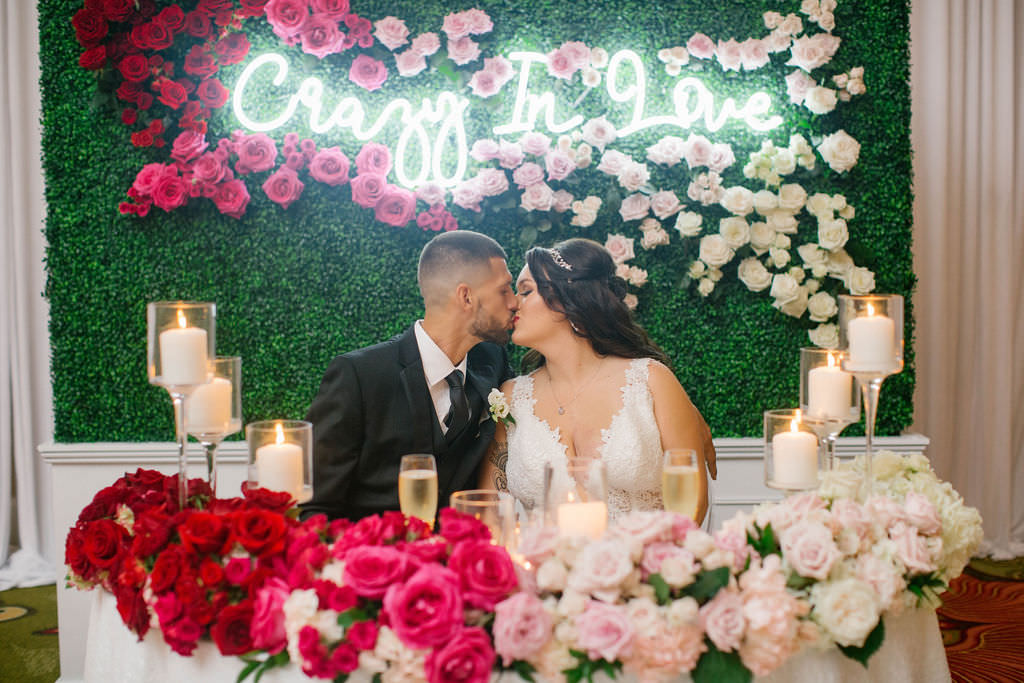 Romantic Bride and Groom at Sweetheart Table with Red, Pink, Blush and Ivory Roses, Glass Candlesticks, Greenery Wall Backdrop with Crazy in Love Neon Sign and Roses | Tampa Bay Wedding Planner Parties A'la Carte | St. Pete Wedding Florist The Vinoy Renaissance | Wedding Hair and Makeup Artist Michele Renee the Studio | Wedding Rentals A Chair Affair | Over the Top Rental Linens