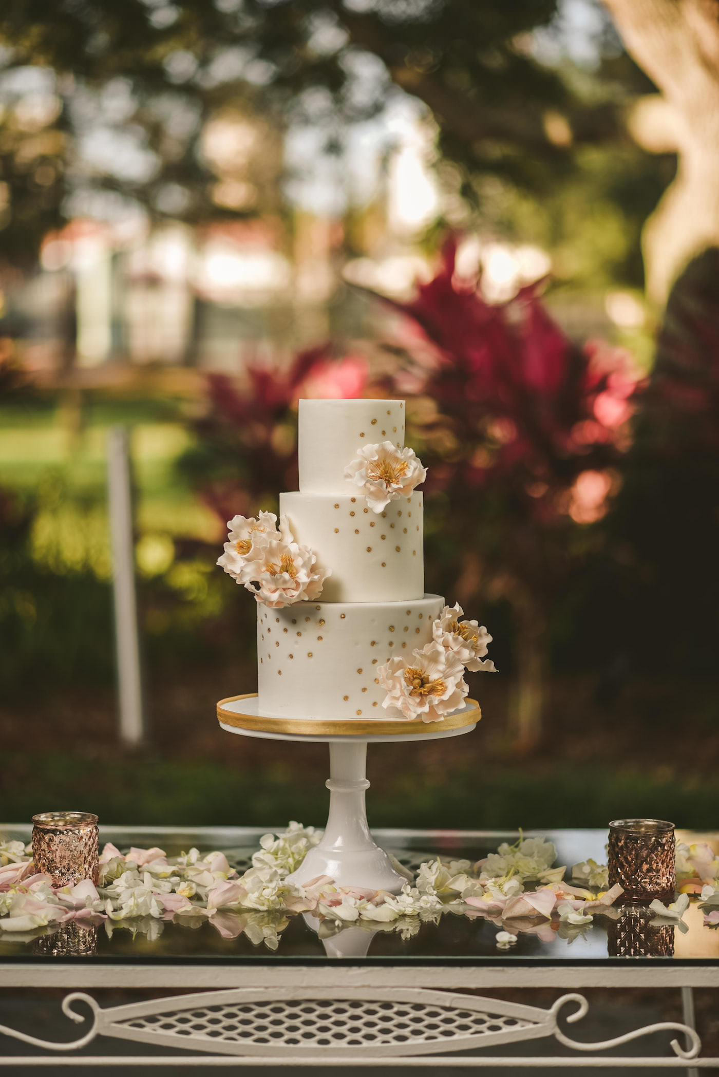 Tampa Bay Cake Company Three Tier Wedding Cake with Rose Gold Polka Dots and Blush Pink Sugar Flower Peonies on a Round Pedestal Cake Stand surrounded by Petals and Candles