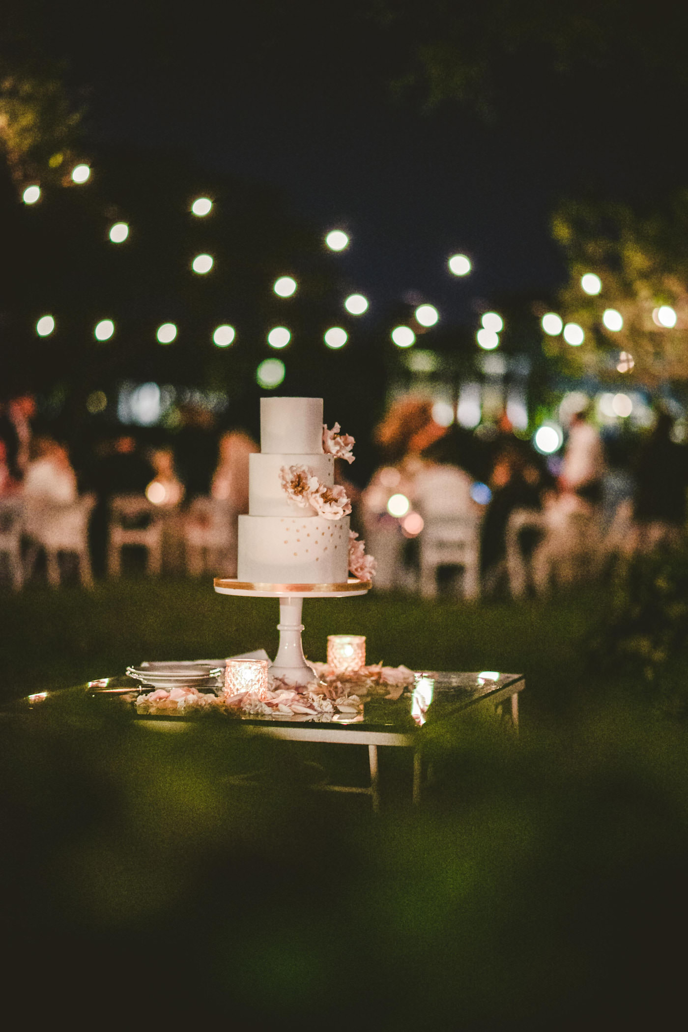 Tampa Bay Cake Company Three Tier Wedding Cake with Rose Gold Polka Dots and Blush Pink Sugar Flower Peonies on a Round Pedestal Cake Stand surrounded by Petals and Candles | Outdoor Tampa Wedding with Canopy String Light Edison Bulb Strands