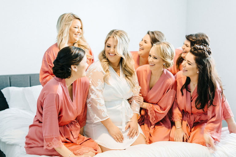 Florida Bride and Bridesmaids Getting Wedding Ready Photo on Bed in Matching Rose Pink Silk Robes