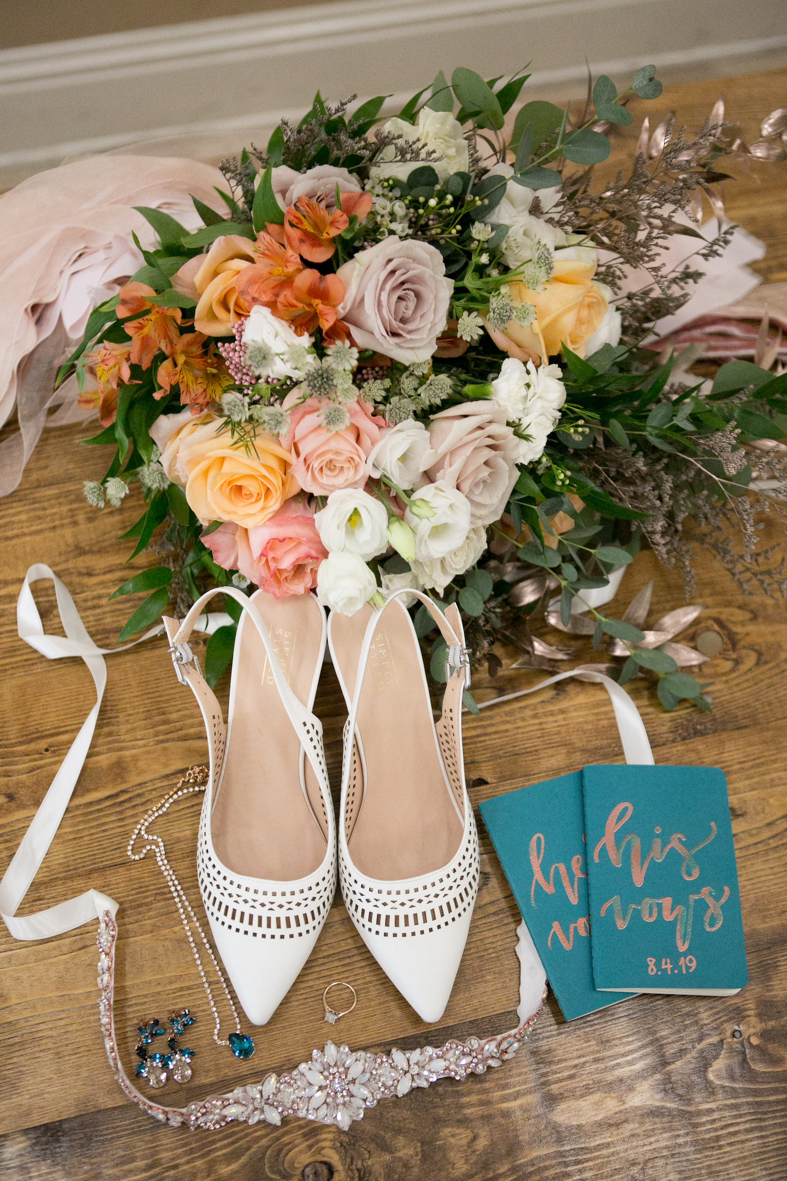 White Pointed Toe Heel Strap Wedding Shoes, Spring Colors Coral, Pink, Orange, Mauve Roses with Greenery Floral Bouquet, Green His and Hers Vows Books, Rhinestone Bridal belt | Wedding Photographer Carrie Wildes Photography