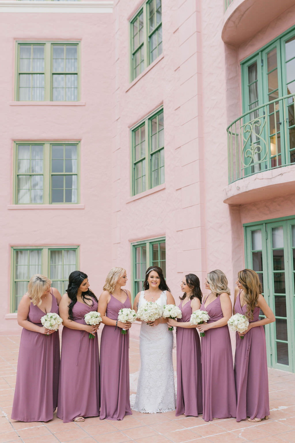 Florida Bride in Lace Wedding Dress and Bridesmaids in Mauve Dresses Holding White Floral Bouquets   St. Petersburg Hotel Wedding Venue The Vinoy Renaissance   Wedding Florist Bruce Wayne Florals   Wedding Hair and Makeup Michele Renee the Studio