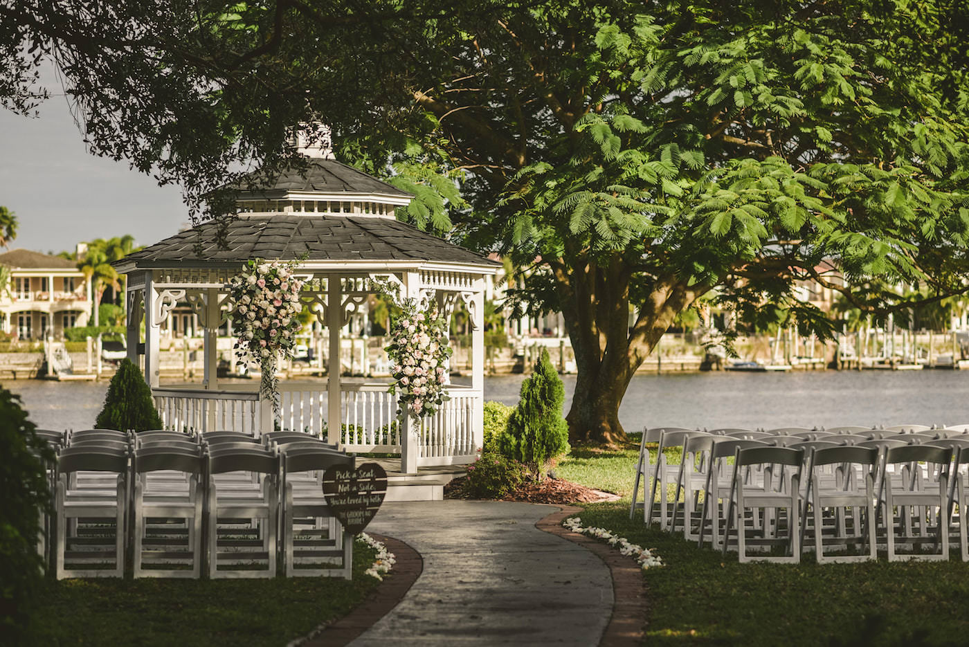 Tampa Wedding Waterfront Garden Ceremony Venue with White and Blush Pink Gazebo Floral Arrangements and White Garden Chairs