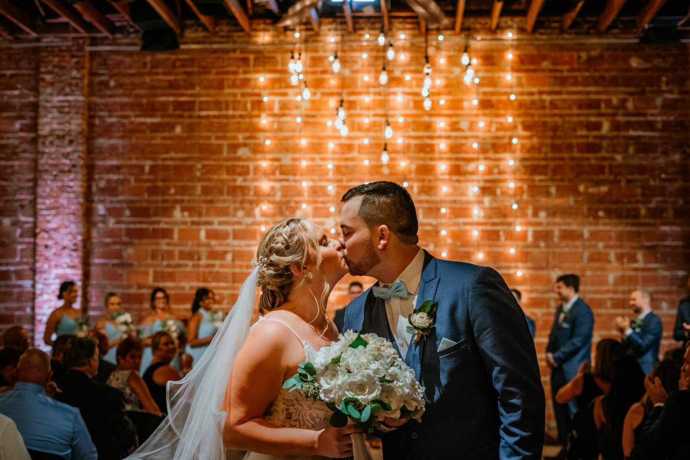 Downtown St. Pete Bride and Groom Intimate Kiss in Indoor Summer Wedding Ceremony, Exposed Red Brick Wall with String Lighting   Tampa Bay Unique Wedding Venue NOVA 535   Florida Wedding Photographer Bonnie Newman Creative   Wedding Hair and Makeup Artist Femme Akoi Beauty Studio