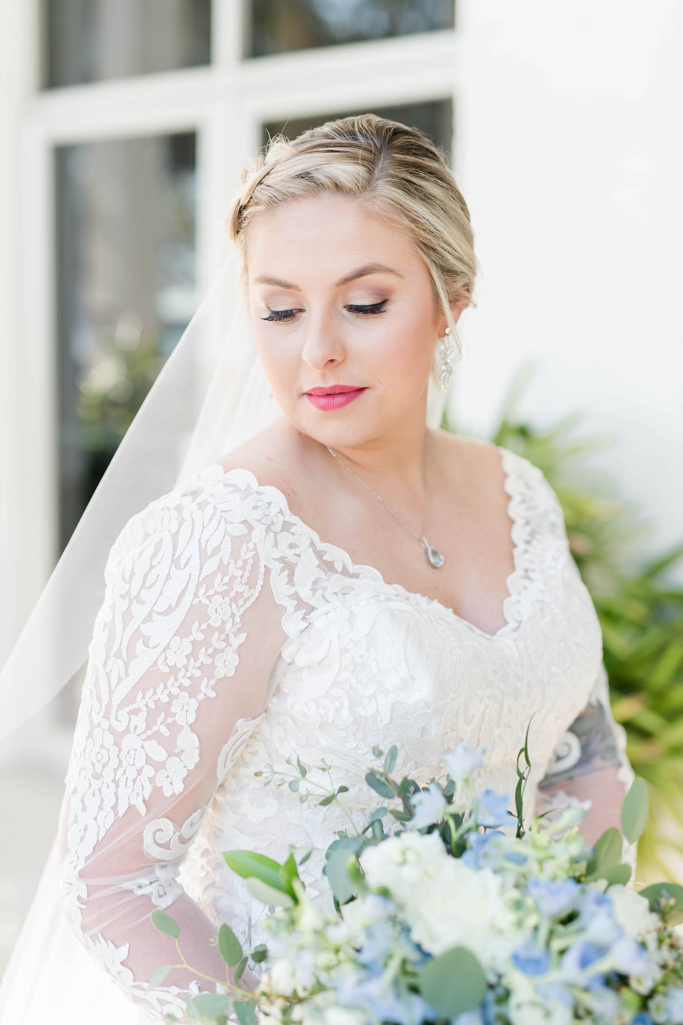 Ivory Lace Long Sleeve Bridal Gown With V Neck   Side Braid Bridal Hairstyle and Natural Wedding Makeup   Blue and White Bridal Bouquet   Femme Akoi Beauty Studio