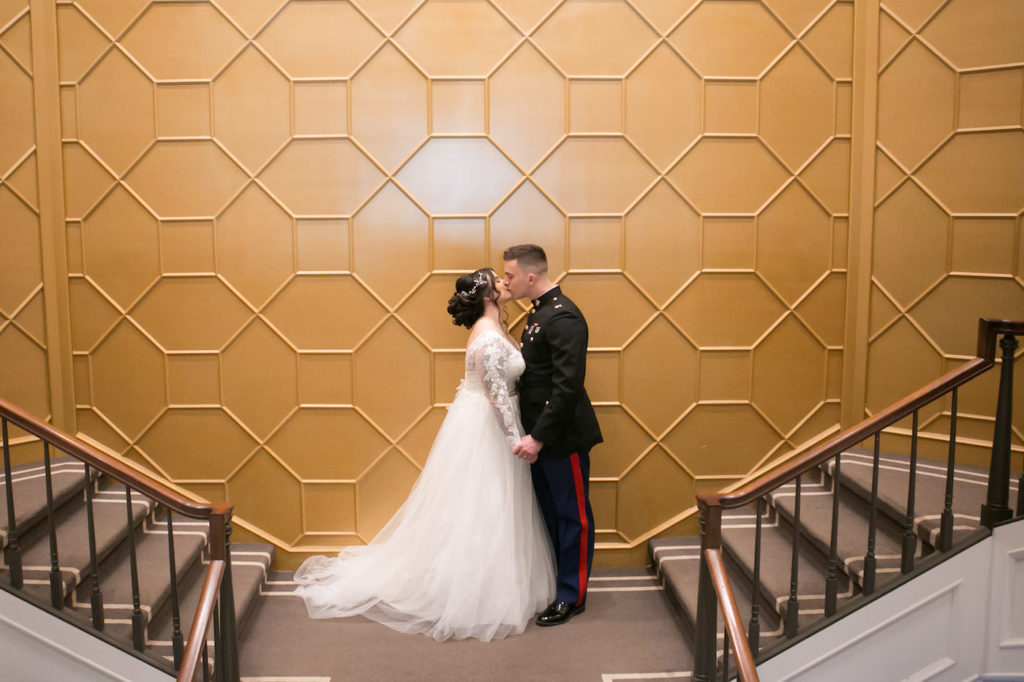 Romantic Bride in Whimsical Empire Waist Long Sleeve Lace and Tulle Wedding Dress and Military Groom in Dress Blues Uniform Kissing First Look Wedding Portrait on Staircase at Wedding Venue The Tampa Club | Wedding Photographer Carrie Wildes Photography