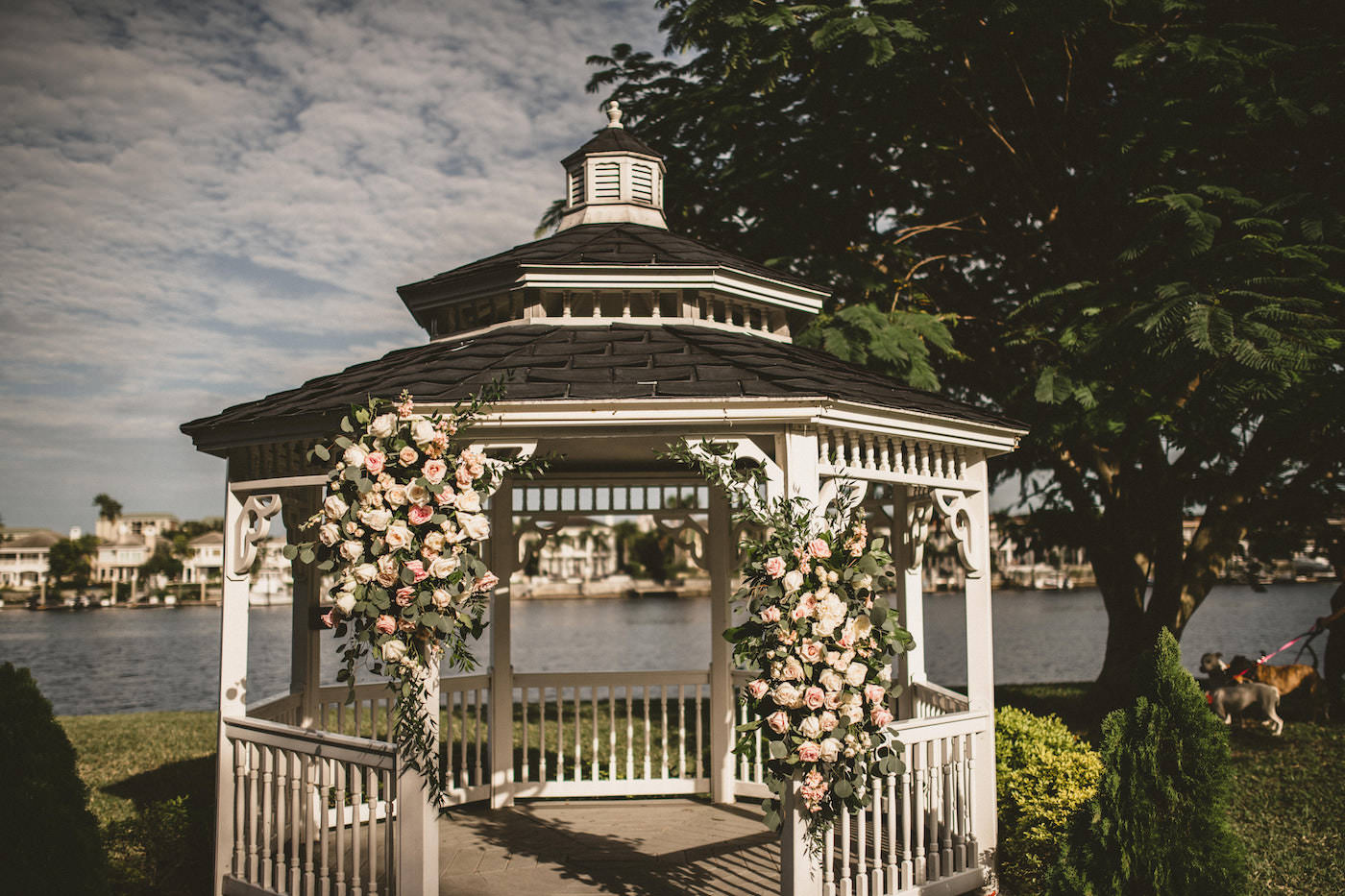 Tampa Wedding Waterfront Garden Ceremony Venue with White and Blush Pink Gazebo Floral Arrangements featuring Roses and Greenery