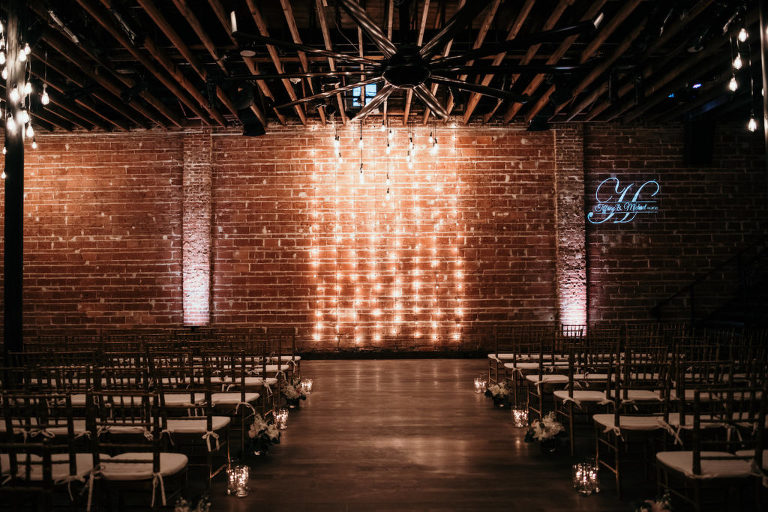 Romantic Interior Florida Wedding Ceremony and Decor, Exposed Red Brick Wall with String Lighting, Chiavari Chairs with Candlelights Down the Aisle | Historic Wedding Venue in Downtown St. Pete NOVA 535