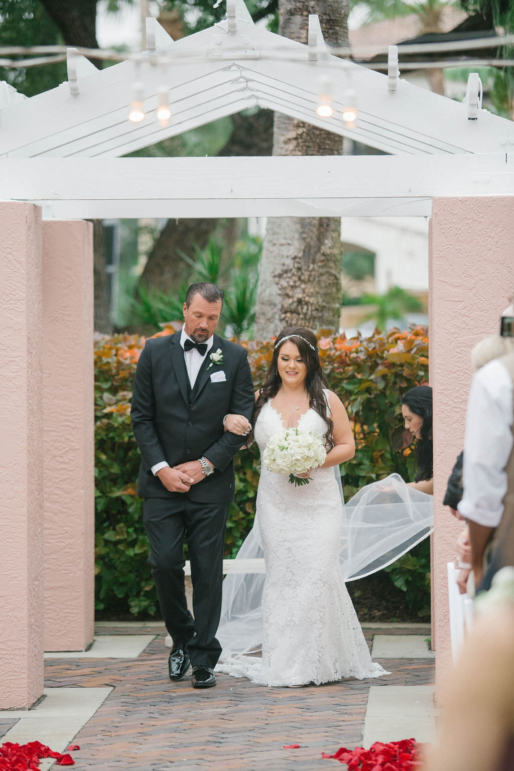 Romantic Bride Walking Down the Wedding Ceremony Aisle in Lace Wedding Dress Holding White Floral Bouquet   Tampa Bay Wedding Florist Bruce Wayne Florals