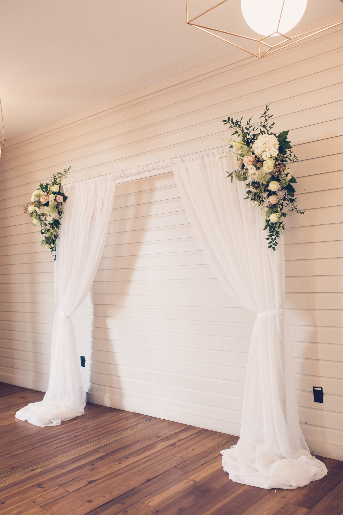Indoor Tampa Wedding Ceremony With Pipe And Drape Fabric Arch Backdrop With Greenery And White Flower Arrangements Marry Me Tampa Bay Local Real Wedding Inspiration Vendor Recommendation Reviews