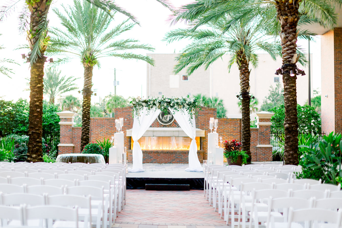 Simple Classic New Year's Eve Wedding Ceremony Decor, Arch with White Draped Linens, Greenery Arrangement and White Florals, Red Brick Fireplace Backdrop, Tampa Agliano Park Courtyard | Wedding Photographer Shauna and Jordon Photography | Wedding Planner UNIQUE Weddings + Events | Wedding Rentals A Chair Affair