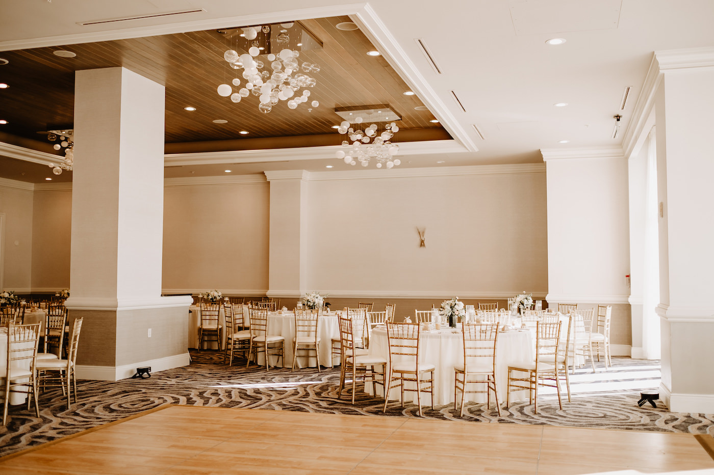 Clearwater Wedding Venue Hyatt Regency Clearwater Beach Hotel   Ballroom Reception with White Table Linens and Gold Chiavari Chairs and Wood Dance Floor with Glass Bubble Chandeliers