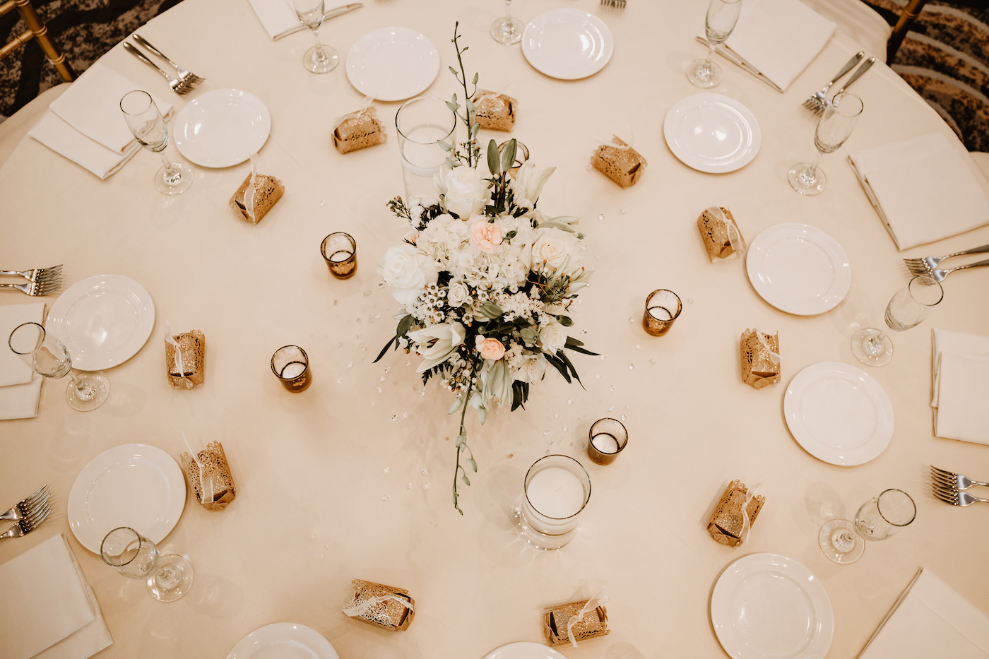 Monochromatic Neutral Wedding Reception Table with White Linens and Gold Votive Candles and White Floral Centerpiece of Ivory Roses Hydrangea Lillies and Orchids