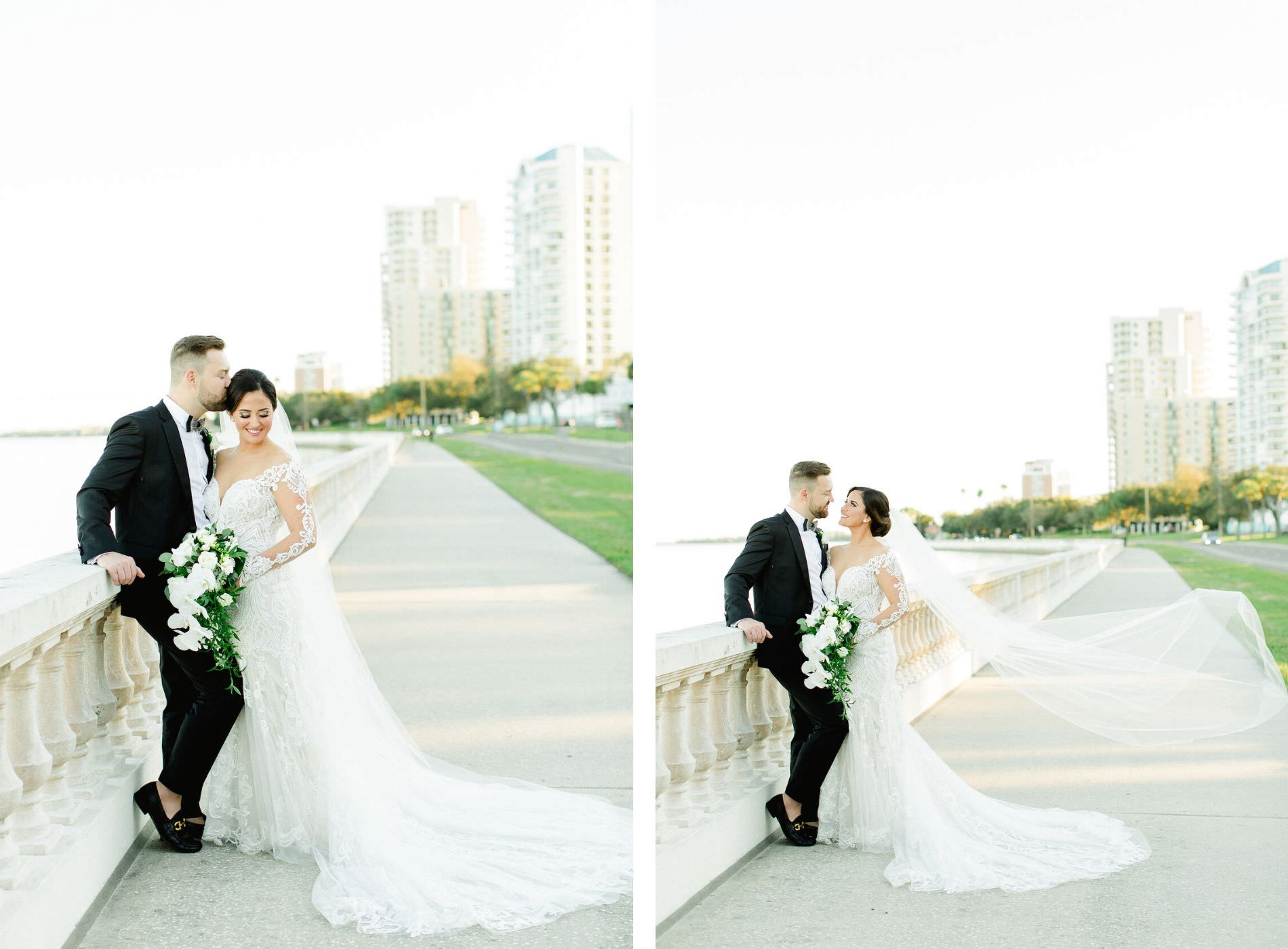 Classic Tampa Bay Bride and Groom Wedding Portrait on Bayshore Boulevard, Bride in Illusion Lace Sleeve Fit and Flare Wedding Dress, Holding Wedding Floral Bouquet with White Orchid, Ivory Roses and Greenery, Veil Blowing in Wind