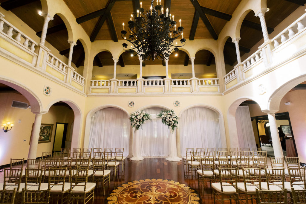 Tampa Wedding Venue Avila Golf & Country Club Indoor Ceremony with Gold Chiavari Chairs, Pipe and Drape Backdrop with Blush Pink and Ivory Rose Floral Arrangements with Greenery and Crystal Chandelier