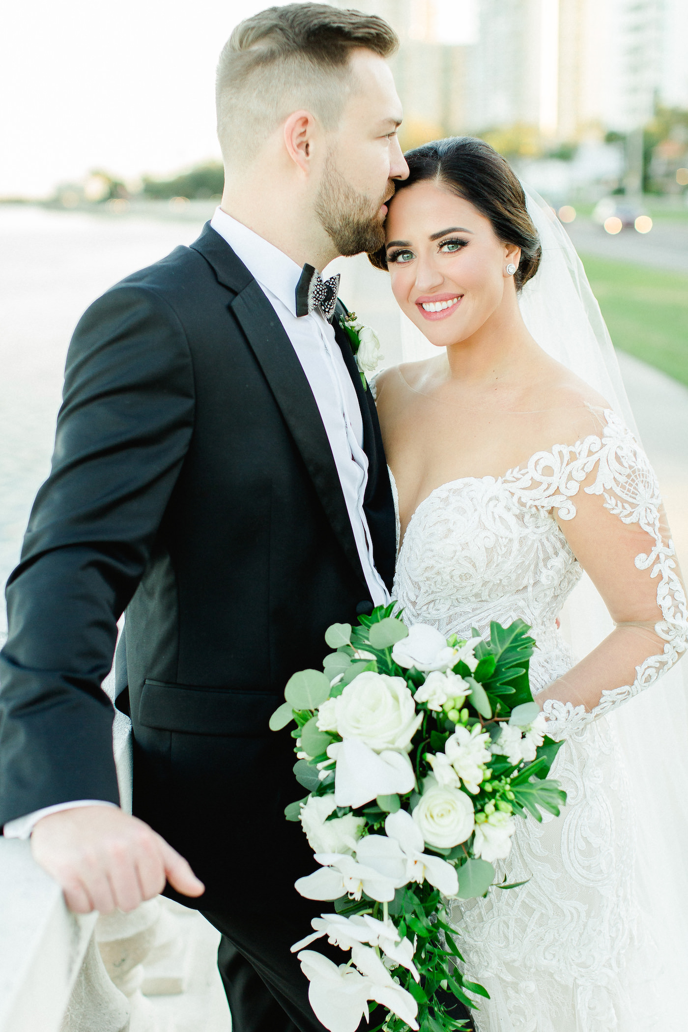 Classic Tampa Bay Bride and Groom Wedding Portrait on Bayshore Boulevard, Florida Bride in Illusion Lace Sleeve Fit and Flare Wedding Dress, Holding Wedding Floral Bouquet with White Orchids, Ivory Roses and Greenery