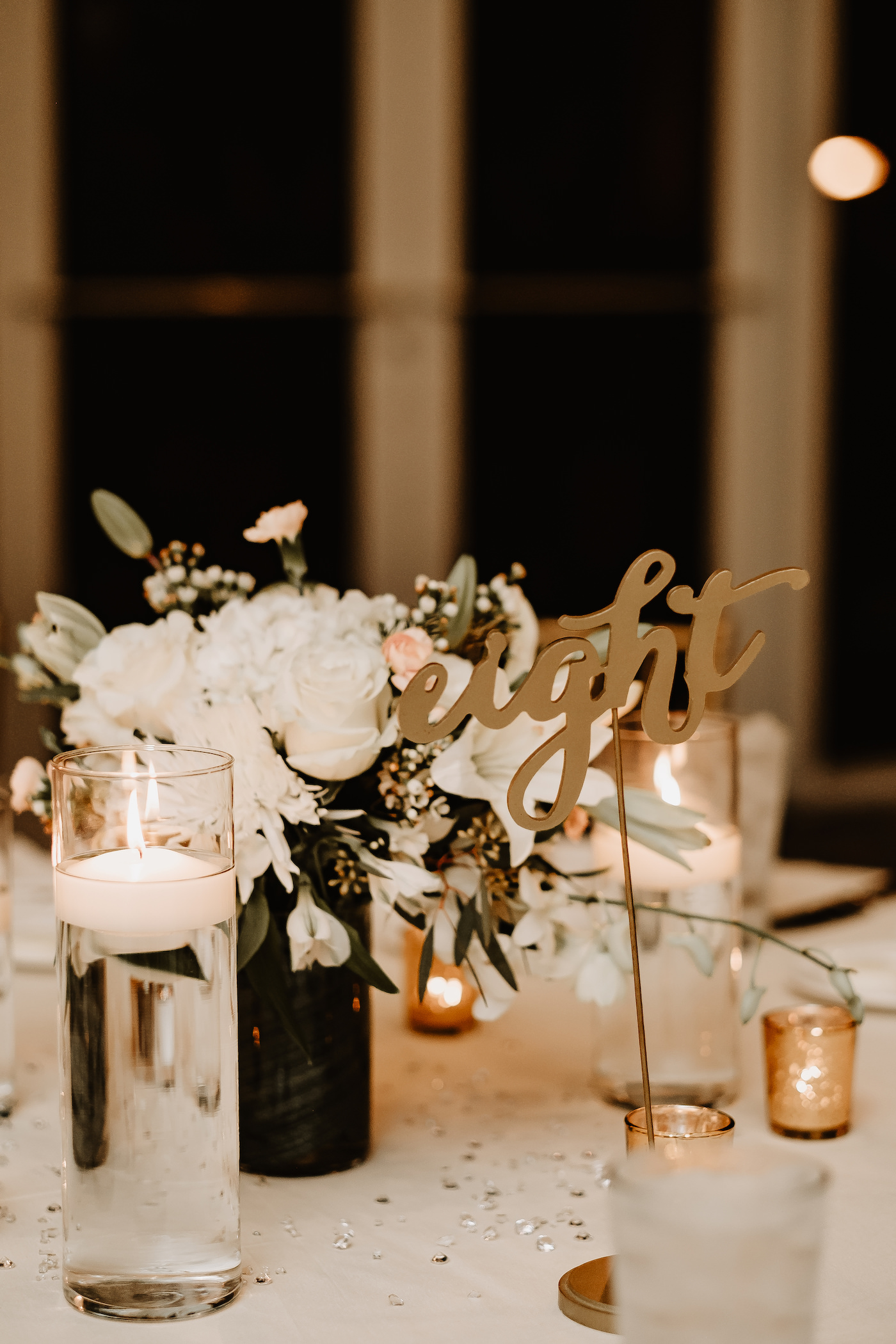 Gold Script Table Number   Gold Votive Candles and White Floral Centerpiece of Ivory Roses Chrysanthemums Lillies and Orchids and Floating Candles