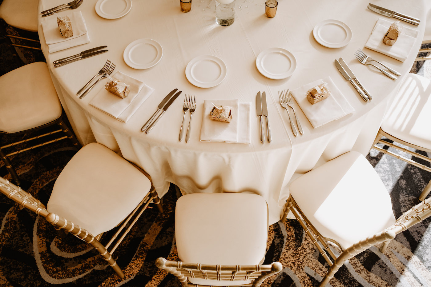 Monochromatic Neutral Wedding Reception Table with Gold Chiavari Chairs and White Linens and Gold Favor Boxes on White Napkins at Place Settings