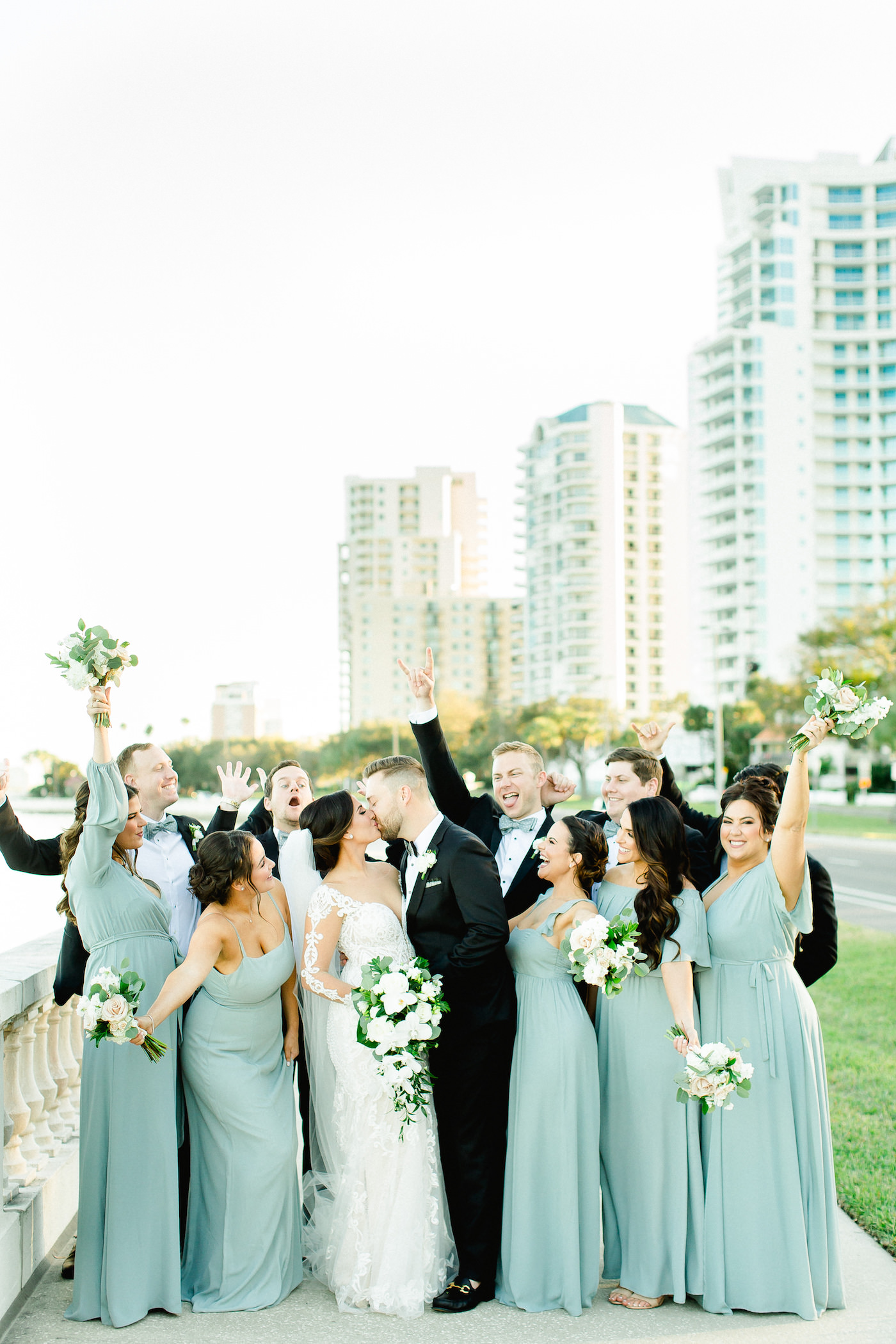 Tampa Bay Fun Wedding Party on Bayshore Boulevard, Bridesmaids in Long Mix and Match Show Me Your Mumu Dresses, Florida Bride in Illusion Lace Sleeve Fit and Flare Wedding Dress, Holding Wedding Floral Bouquet with White Orchids, Ivory Roses and Greenery | Florida Wedding Planner Breezin' Weddings
