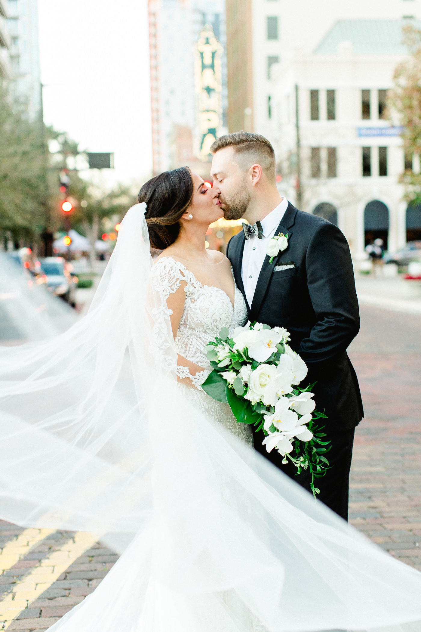 Classic Tampa Bay Bride and Groom Wedding Portrait in downtown Tampa, Florida Bride in Illusion Lace Sleeve Fit and Flare Wedding Dress, Holding Wedding Floral Bouquet with White Orchids, Ivory Roses and Greenery, Veil Blowing in Wind